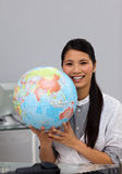 Confident businesswoman holding a globe Royalty Free Stock Images