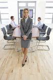 Confident businesswoman holding laptop in conference room Stock Photo