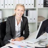 Confident Businesswoman Holding Paper At Desk Stock Photos