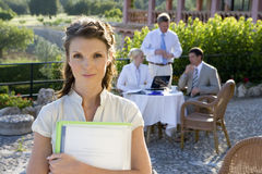 Confident businesswoman holding paperwork at caf? with coworkers in background.  Royalty Free Stock Image
