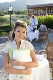 Confident businesswoman holding paperwork at caf? with coworkers in background Stock Photo