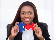 Confident businesswoman holding puzzle pieces in office Royalty Free Stock Photo
