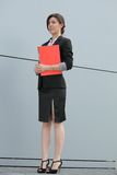 Confident businesswoman holding a red folder Royalty Free Stock Photo