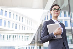 Confident businesswoman holding tablet PC outside office building royalty free stock image