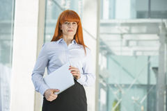 Confident businesswoman looking away while holding laptop in office Royalty Free Stock Photos