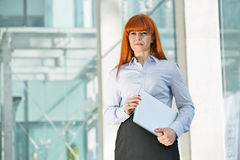 Confident businesswoman looking away while holding laptop in office Stock Photos