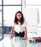 Confident businesswoman looking at the camera. Confident businesswoman smiling at the camera in a presentation Royalty Free Stock Photography