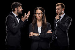 Confident businesswoman looking at camera while her colleagues discussing something behind. Isolated on black Stock Photos