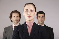 Confident Businesswoman With Male Colleagues In Background Stock Image