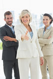 Confident businesswoman offering handshake with team in office Royalty Free Stock Images