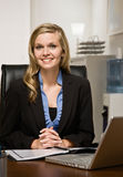Confident businesswoman reading report at desk Stock Photography