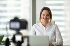 Confident businesswoman recording video course on camera. Successful businesswoman smiling recording video for online business course, confident female coach stock images