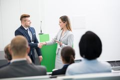 Businesswoman Shaking Hands With Male Colleague In Front Of Audi. Confident businesswoman shaking hands with colleague in front of audience at lecture hall Royalty Free Stock Image