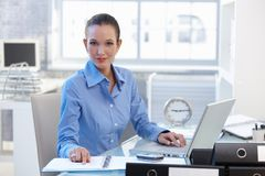 Confident businesswoman sitting at desk Stock Photo
