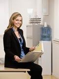 Confident businesswoman sitting on desk Royalty Free Stock Photos