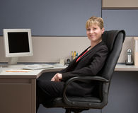 Confident businesswoman sitting at desk in cubicle. Happy, confident businesswoman sitting at desk in cubicle Stock Photography