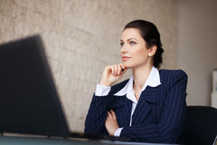 Confident businesswoman sitting at desk in office Royalty Free Stock Image