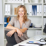 Confident Businesswoman Sitting At Desk Royalty Free Stock Photography