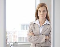 Confident businesswoman smiling in bright office Royalty Free Stock Images