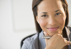 Confident Businesswoman Smiling With Hand On Chin Stock Photo