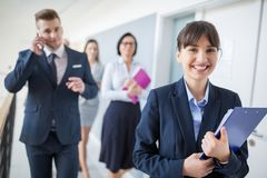Confident Businesswoman Smiling While Walking With Team. Portrait of confident businesswoman smiling while walking with team in office royalty free stock image