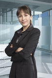Confident Businesswoman Standing Arms Crossed In Office Stock Photography