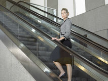 Confident Businesswoman Standing On Escalator Stock Photo