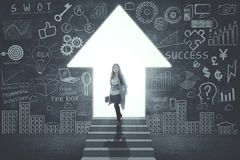 Confident businesswoman standing in front of door in form of up arrow Royalty Free Stock Photography