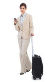 Confident businesswoman with suitcase and phone Royalty Free Stock Image