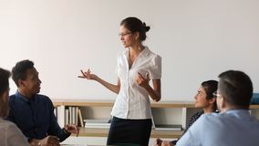Confident businesswoman talk holding meeting with diverse colleagues stock images