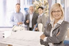Confident businesswoman with team stock images