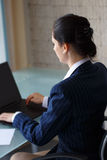 Confident businesswoman typing on laptop back view Royalty Free Stock Image