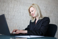 Confident businesswoman typing on laptop Stock Image