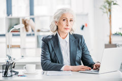 Confident businesswoman typing on laptop at workplace in modern office Stock Images