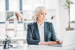 Confident businesswoman typing on laptop at workplace in modern office Royalty Free Stock Photos