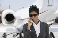 Confident Businesswoman Using Cellphone At Airfield. Confident businesswoman using cell phone with airplane in the background at airfield Royalty Free Stock Photo