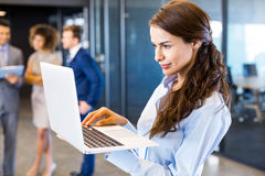Confident businesswoman using laptop in office Stock Photos