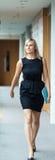 Confident businesswoman walking through a corridor Stock Images