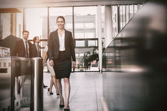 Confident businesswoman walking in office Stock Photo