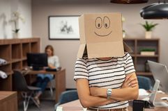 Woman wearing happy face cardboard in office royalty free stock photo