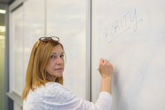 Confident businesswoman writing word priority on whiteboard in m stock photo