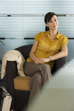 Confident businesswoman in yellow short-sleeved blouse sitting in office chair, portrait Royalty Free Stock Images