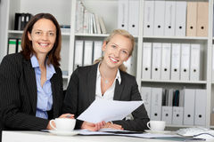 Confident Businesswomen Sitting At Office Desk Royalty Free Stock Image