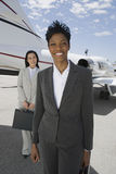 Confident Businesswomen Standing At Airfield Stock Photos