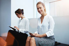 Confident businesswomen using digital tablet and cell telephone during break between conference Stock Photos