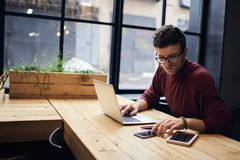 Man freelancer surfing net searching information for presentation. Confident busy male freelancer in trendy eyewear doing remote job using modern technologies Stock Image