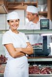 Confident Butcher With Colleague Working In Shop Stock Photo