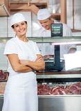 Confident Butcher With Colleague Working In Store Stock Photo