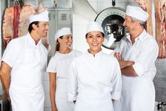 Confident Butcher With Colleagues In Butchery Stock Images