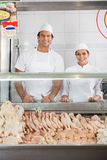 Confident Butchers Smiling At Display Cabinet Stock Photo